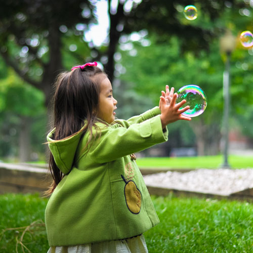 A girl playing with bubbles in a park